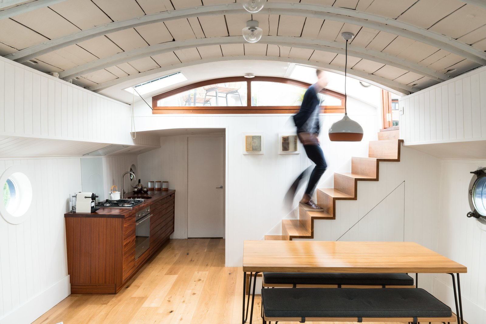 A dipped terracotta pendant light by Hand and Eye Studio London hangs above the  Brunel by Heals dining table and benches. Tagged: Dining Room, Table, Accent Lighting, Bench, Light Hardwood Floor, and Pendant Lighting.  Photo 3 of 9 in Londoners Can Live in This Scandinavian-Inspired, Converted Barge For $424K