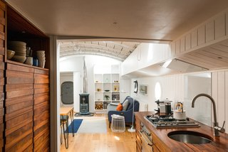 Londoners Can Live in This Scandinavian-Inspired, Converted Barge For $424K - Photo 4 of 9 - A Saikai Kaico Japanese enamel kettle and hand thrown dishes by David Green Ceramics sit proudly in the galley kitchen.