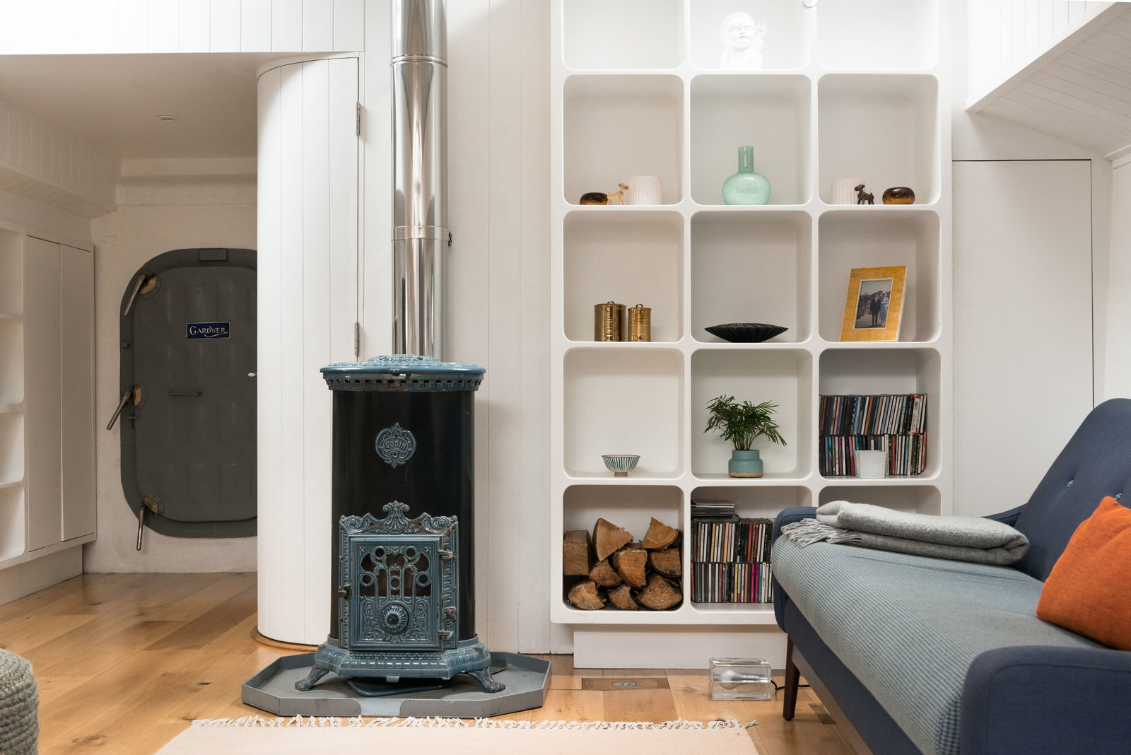 An original 1920's restored Goodin Woodburning Stove anchors the cozy living space. Tagged: Living Room, Light Hardwood Floor, Shelves, Wood Burning Fireplace, and Sofa.  Photo 5 of 9 in Londoners Can Live in This Scandinavian-Inspired, Converted Barge For $424K