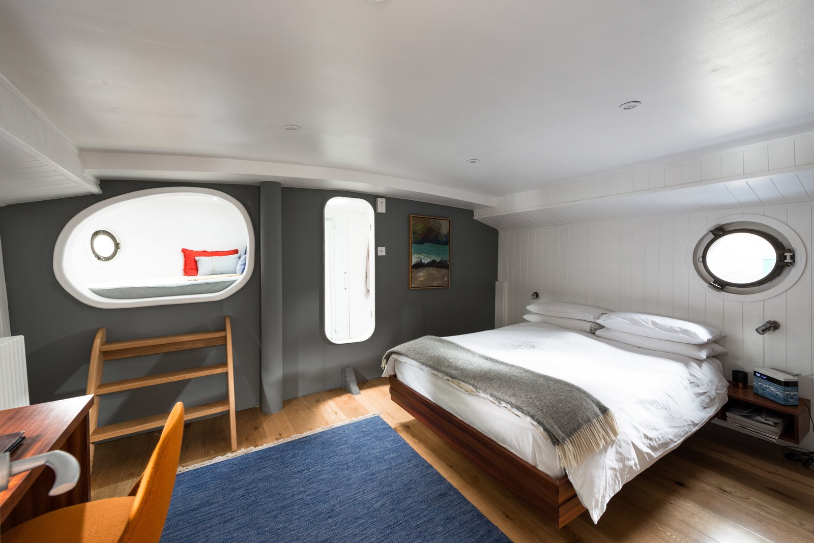 The Master Bedroom includes a private en-suite, desk, and Tagged: Bedroom, Bed, Wall Lighting, Light Hardwood Floor, and Rug Floor.  Photo 7 of 9 in Londoners Can Live in This Scandinavian-Inspired, Converted Barge For $424K