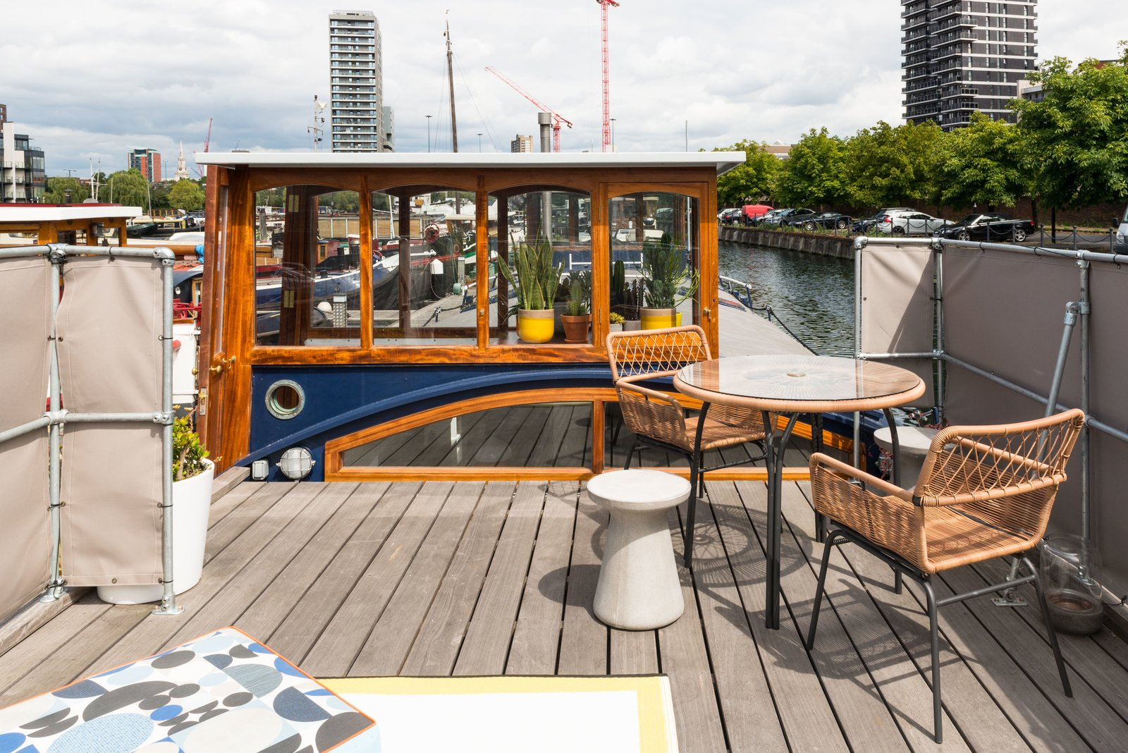 A round concrete stool, table and chairs, custom cushions, and outdoor rug create a perfect terrace setting to look out to the city beyond. Tagged: Outdoor, Rooftop, and Wood Patio, Porch, Deck.  Photo 9 of 9 in Londoners Can Live in This Scandinavian-Inspired, Converted Barge For $424K