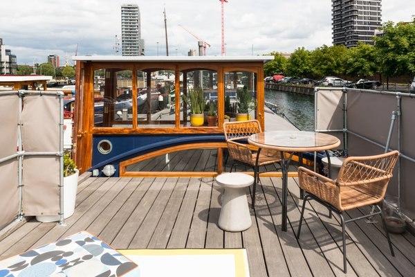 A round concrete stool, table and chairs, custom cushions, and outdoor rug create a perfect terrace setting to look out to the city beyond.  Photo 9 of 9 in Londoners Can Live in This Scandinavian-Inspired, Converted Barge For $424K