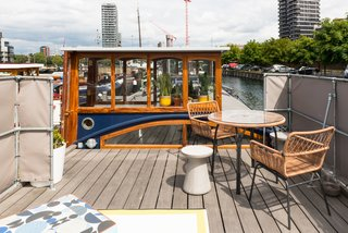 Londoners Can Live in This Scandinavian-Inspired, Converted Barge For $424K - Photo 9 of 9 - A round concrete stool, table and chairs, custom cushions, and outdoor rug create the perfect terrace setting to look out to the city beyond.