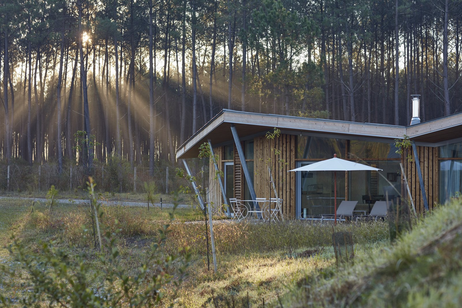 Maritime pines from the Landes Forest compose the exterior wood cladding of each hut and purposefully form the incredible views outward to the lake. The wood frame segues into an angular, butterfly roof that collects and directs rainwater back into the lake. Furthermore, it provides shading where full-height windows open into the living space. By orienting each hut in the same direction, the architects create a sense of isolation within the wood enclosure.
