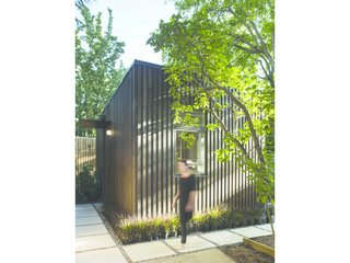 A Modern Micro-House in Portland Clad in Local Fir - Photo 8 of 8 - Light and shadow play on the textured facade. Greenery frames the simple, geometric form of the house.