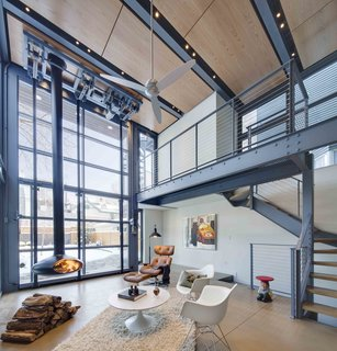 A Steel-and-Glass Addition With a Giant Hangar Door Maximizes Indoor/Outdoor Living - Photo 5 of 9 - The interior living space is warmed by the wood panels above and a hanging fireplace.