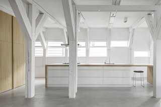 A Converted Warehouse in Amsterdam Boasts Soothing Interiors of Concrete and Wood - Photo 1 of 9 - The fully-integrated kitchen is obscured by oak cabinetry, corresponding with a large island with an integrated cooktop and sink.