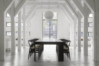 A Converted Warehouse in Amsterdam Boasts Soothing Interiors of Concrete and Wood - Photo 2 of 9 - Hans J. Wegner Wishbone Chairs surround the large dining table on axis with the grand, exterior windows.