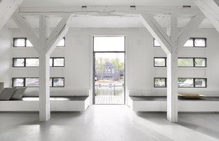 A Converted Warehouse in Amsterdam Boasts Soothing Interiors of Concrete and Wood - Photo 3 of 9 - Existing, renovated windows provide ample daylight and views of the surrounding shipyard.