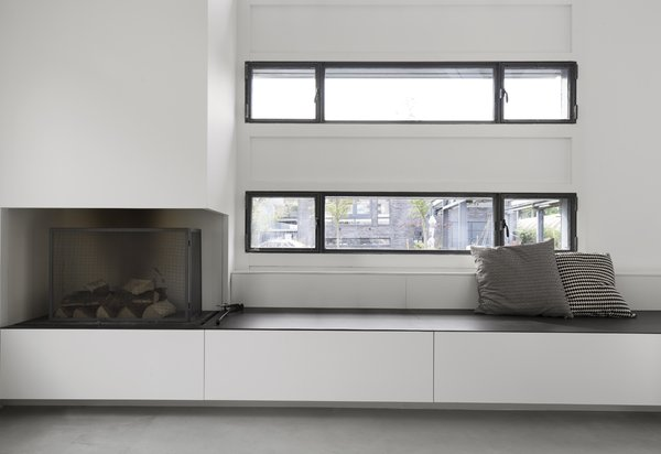 Custom millwork benches with integrated storage and even a fireplace, sit below the windows, lining the exterior walls of the open living space.