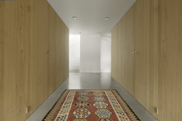 The white stair ascends upward as a light-filled sculptural element.