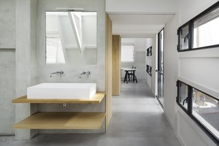 A Converted Warehouse in Amsterdam Boasts Soothing Interiors of Concrete and Wood - Photo 7 of 9 - A custom solid surface basin on oak wooden shelves, in combination with a Zuchetti faucet and a Vibia Linestra light fixture, make for a warm, contemporary bath vanity.