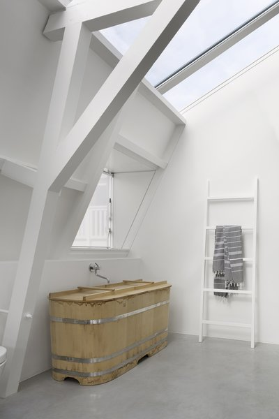 A traditional Japanese style bathtub, custom ordered and made by Bartok design sits elegantly in one of the baths.