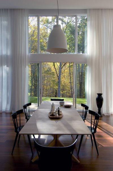 The dining space is directly connected to the outdoors through sliding glass doors and views to the trees beyond.