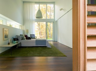 A Cedar- and Metal-Clad Shed House Ushers In the Outdoors - Photo 8 of 11 - Large windows continue into the master bedroom. A green rug connects the colors of the exterior with the interior space.