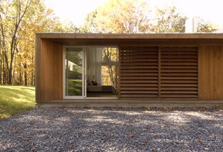 A Cedar- and Metal-Clad Shed House Ushers In the Outdoors - Photo 11 of 11 - Wooden screens provide privacy to the master bedroom from the entrance facade.