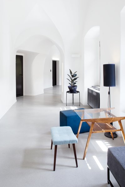 Mid-century modern furniture pieces with blue pastel upholstery and warm wood tones accent the white, bright corridors.