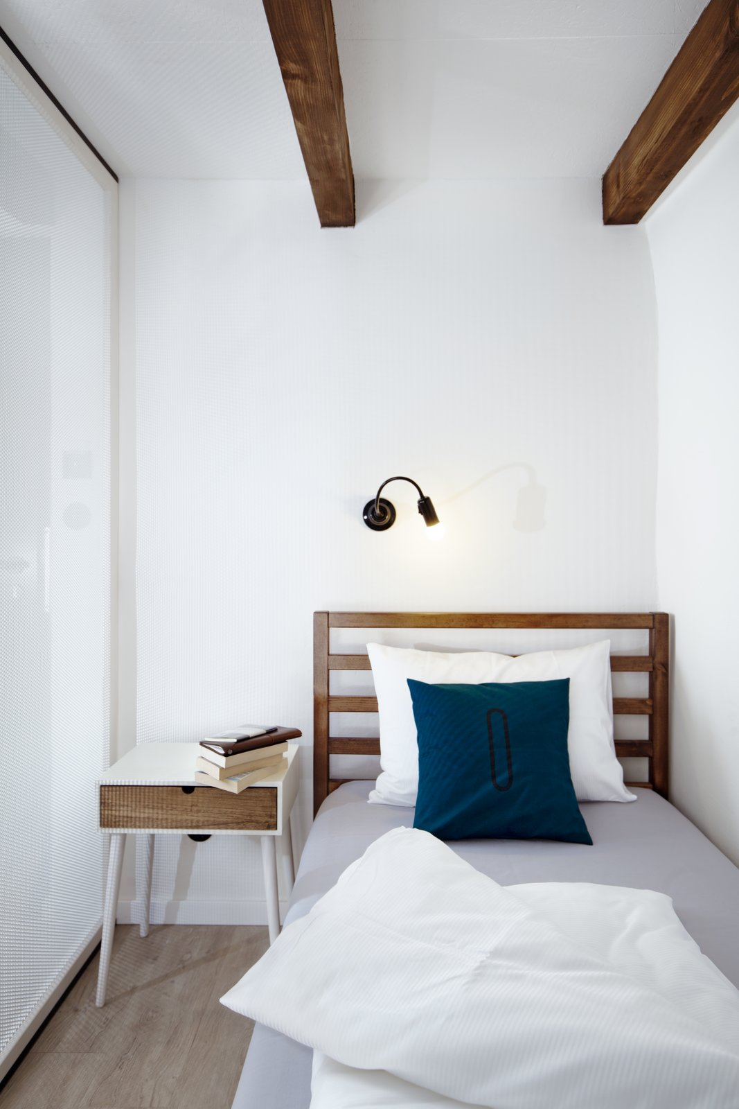Wooden beams, wood floors, and wood furniture pieces introduce raw elements and textures. Tagged: Bedroom, Wall, Bed, Night Stands, and Light Hardwood.  Best Bedroom Night Stands Photos from A Stylish Hostel in a Historic Czech Fortress Starts at $16 a Night