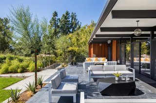 An Award-Winning Midcentury Residence in Los Angeles County Asks $3.9M - Photo 3 of 17 - Exterior overhangs provide shading for exterior seating, while also protecting the interior from the warm, summer sun.
