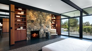 An Award-Winning Midcentury Residence in Los Angeles County Asks $3.9M - Photo 6 of 17 - Built-in bookshelves frame each side of the stone fireplace.