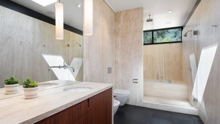 An Award-Winning Midcentury Residence in Los Angeles County Asks $3.9M - Photo 7 of 17 - Natural tile brings the natural elements into the luxurious bath while transom windows bring in daylight.