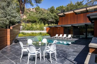 An Award-Winning Midcentury Residence in Los Angeles County Asks $3.9M - Photo 14 of 17 - The pool, accessed from the main level, is surrounded by the same dark floor finish as the interior. Bright white chairs and loungers contrast with the dark materials.