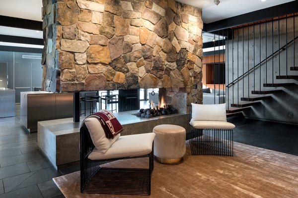 A two-sided fireplace visually connects the living spaces.  Open tread stairs hang from the floor above.