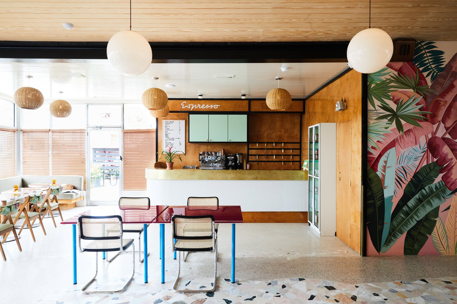 The Lobby Reception space is adorned with mid-century modern pendant lighting, tropical wall graphics,  and color furnishings. Tagged: Dining Room, Chair, Table, Bar, Pendant Lighting, Bench, Terrazzo Floor, and Ceiling Lighting.  Best Photos from This Revived New Orleans Motel Has Some Serious Flair