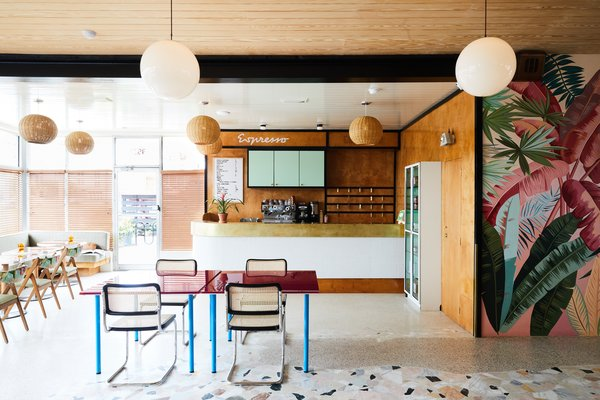The Lobby Reception space is adorned with mid-century modern pendant lighting, tropical wall graphics,  and color furnishings.