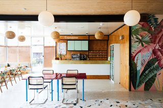This Revived New Orleans Motel Has Some Serious Flair - Photo 3 of 11 - The lobby and reception space is adorned with retro pendant lighting, tropical wall graphics,  and colorful furnishings.