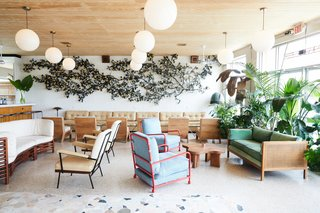 This Revived New Orleans Motel Has Some Serious Flair - Photo 5 of 11 - A mix of contemporary and 1950's furnishings fill the lobby bar space, accented with greenery and globe pendant lights. A floral art installation, crafted from Ralph Lauren shirts, stretches across the wall.