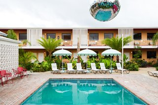 This Revived New Orleans Motel Has Some Serious Flair - Photo 10 of 11 - A cantilevered disco ball hangs over the courtyard pool, while guest room balconies overlook the shared communal space.  What was previously a concrete parking lot has been transformed into a lush, tropical courtyard.