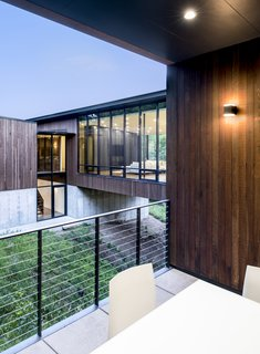 An Incredible Forest Home Leaps Over a Ravine - Photo 4 of 9 - Despite large amounts of glass, the house provides spaces of refuge. The outdoor patio is nestled into the hillside, sheltered by the landscape and building.