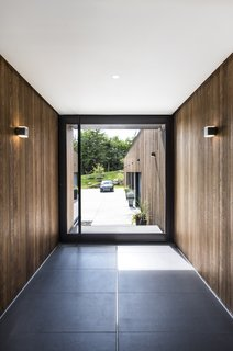 An Incredible Forest Home Leaps Over a Ravine - Photo 2 of 9 - Cedar walls and Bega wall sconces seamlessly extend from exterior to interior.