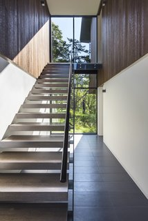 An Incredible Forest Home Leaps Over a Ravine - Photo 5 of 9 - Open stair treads, composed of rift sawn white oak with a custom stain, allow light to pass through.