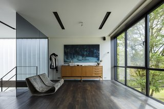 A Fantastic Renovation in Belgium Rescues a Bauhaus-Inspired Home - Photo 10 of 11 - Chairs by Willy Guhl, a cabinet by Pieter De Bruyne, and artwork by Xavier Visa decorate a sitting area on the upper floor, flanking the steel staircase.