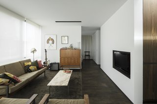 A Fantastic Renovation in Belgium Rescues a Bauhaus-Inspired Home - Photo 11 of 11 - The living space is anchored by a marble coffee table created by Poul Kjaerholm and a wooden cabinet by Pieter De Bruyne.