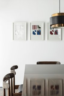 A Fantastic Renovation in Belgium Rescues a Bauhaus-Inspired Home - Photo 9 of 11 - Artwork by Jean-Pierre Murray accents the dining space furnished with Alfred Hendrickx table and chairs.