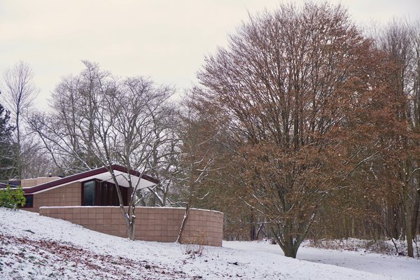 A curved concrete block wall conceals one of the three exterior terraces.  Low-slung roofs appear to hover above the landscape.