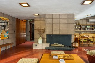 You Can Now Rent Frank Lloyd Wright's Gloriously Restored Eppstein House - Photo 3 of 13 - Living and dining spaces wrap around the full-height fireplace.  Original light fixtures remain and have been outfitted with LED lights.