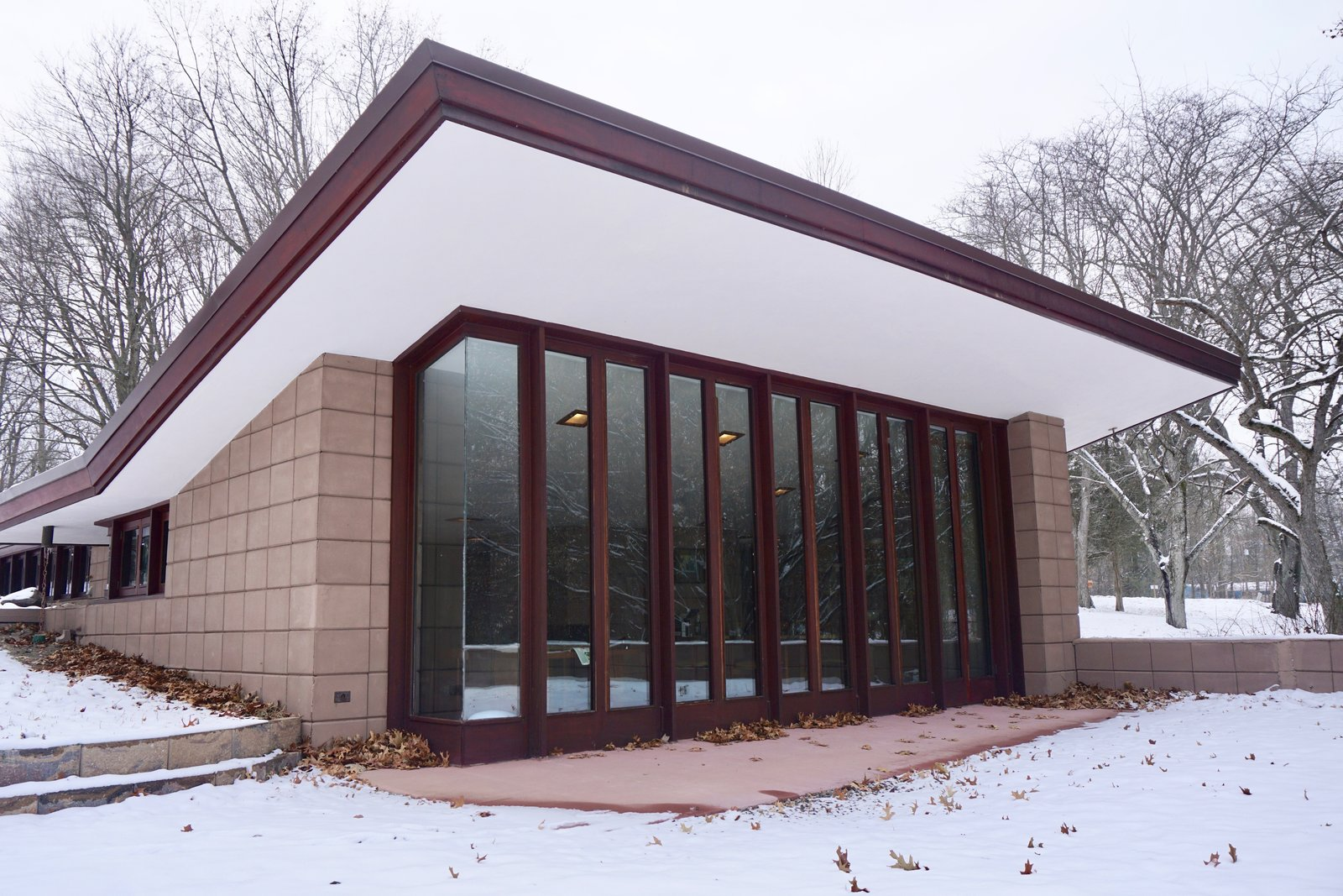 The cantilevered roofs and trim have been carefully painted and restored.  Large windows blend the exterior terrace with the inside living space.