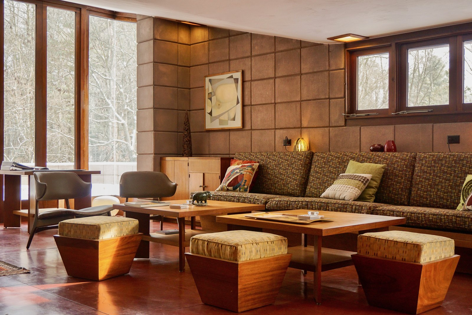 The original built in sofa remains in the Living Room.  Ten foot windows draw nature inside while Maharam and Knoll textiles decorate the furnishings.