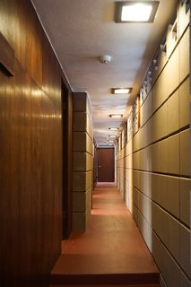 You Can Now Rent Frank Lloyd Wright's Gloriously Restored Eppstein House - Photo 9 of 13 - Refinished concrete floors extend down the gallery corridor. Perforated concrete blocks act as transom windows to fill the corridor with light. Mahogany woodwork and doors lead to the sleeping spaces.