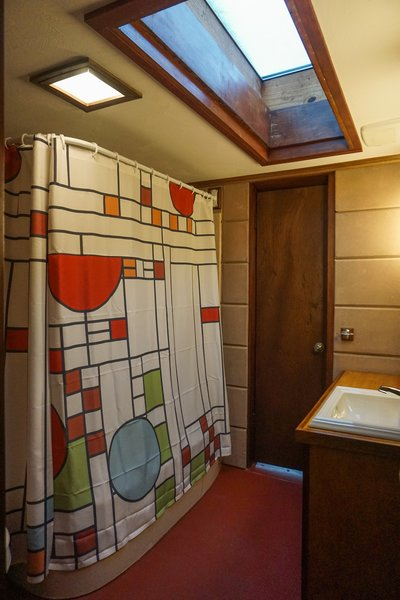 A large, wood framed skylight fills the master bath with daylight.  A Frank Lloyd Wright inspired shower curtain accents the remodeled bath.