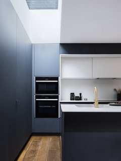 A Sleek Renovation in London Ushers Light Into a Family Home - Photo 6 of 11 - Plywood covered with Fenix NTM forms the kitchen cabinetry and surfaces. A Cascata satin bronze tap by Olif adds a metallic element.
