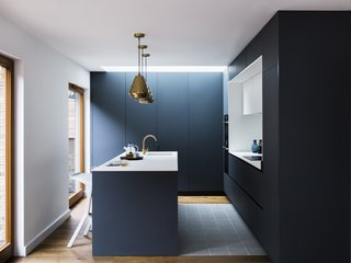 A Sleek Renovation in London Ushers Light Into a Family Home - Photo 7 of 11 - Aston pendants by House Doctor match the metallic hue of the tap. White Miura Stools by PLANK provide seating at the island.