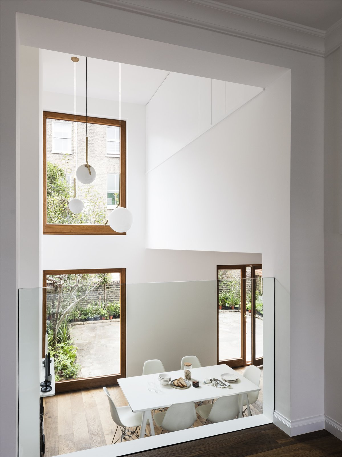 Large windows fill the main living and dining space with natural light.  FLOS IC Pendant Lights hang in the double height space. Tagged: Dining Room, Chair, Table, Pendant Lighting, and Medium Hardwood Floor.  Best Photos from A Sleek Renovation in London Ushers Light Into a Family Home