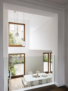 A Sleek Renovation in London Ushers Light Into a Family Home - Photo 2 of 11 - Large windows fill the main living and dining space with natural light.  FLOS IC Pendant Lights hang in the double height space.