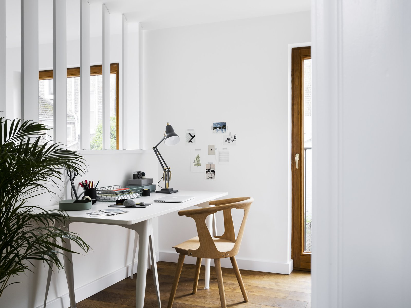 An IKEA desk and SKI wooden provide working accommodations in the study, overlooking the main living space. Tagged: Office, Study, Chair, Desk, Lamps, and Medium Hardwood Floor.  Best Photos from A Sleek Renovation in London Ushers Light Into a Family Home