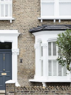 A Sleek Renovation in London Ushers Light Into a Family Home - Photo 1 of 11 - The renovated home maintains some of the original character. From the front elevation, the contemporary refurbishments are concealed.